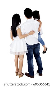 Back view of Asian family standing in the studio while embracing each other, isolated on white background