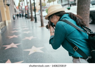 back view of asian female photographer taking photos of star sign on street in Hollywood Boulevard by professional lens camera. young girl traveler major tourist destination in Los Angeles usa spring