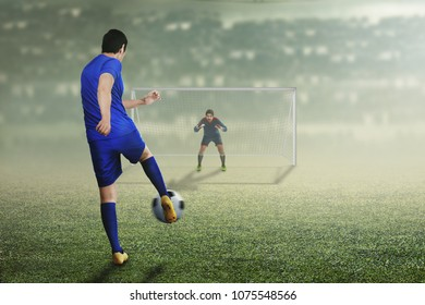 Back view of asian football player man in action on the stadium field