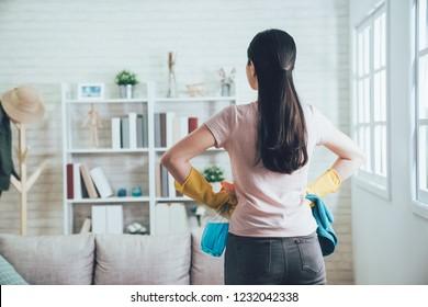 整理整頓後の清潔な居間を見るアジアの家政婦の背景。若い妻は家事を終え、手を腰につけ、日差し窓の傍らの本棚を見つめた。