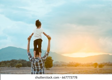 Back view of asian little girl standing on father's shoulder and playing together in the cornfield at sunset in vintage color tone