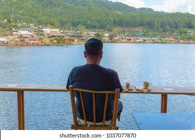 back view asian male wear black shirt and hat, drinking coffee at wooden terrace near the lake  with amazing panorama view of local village in the mountain. travel,leisure concept.