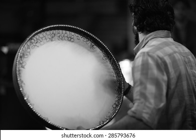 Back view of an asian musician playing daf drum, persian music