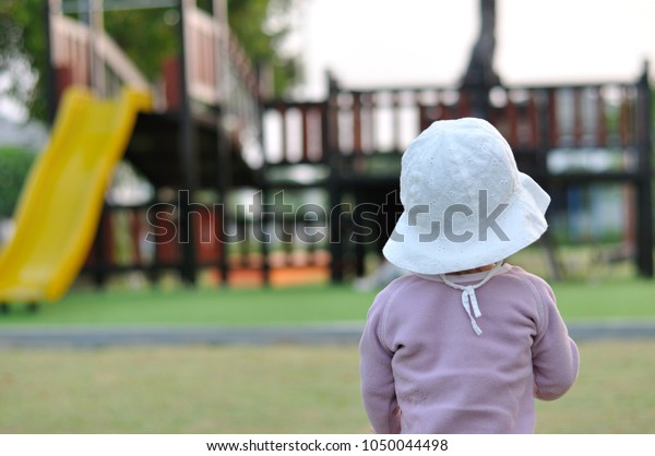 Back view of asian toddler in white hat and light violet long sleeves T shirt looking at playground in a park