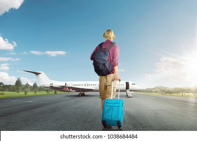 Back view of asian traveler man walking with suitcase to airplane in the runway