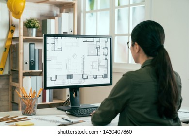 back view of asian woman architect in shirt looking on internet online blueprint document project of green building. female interior designer worker working desktop computer monitor typing keyboard