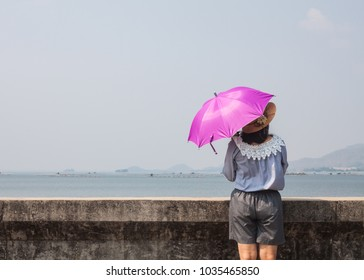 back view asian women wear umbrella with sunlight rays