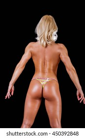 Back view of athletic blond female isolated on a bleck background.