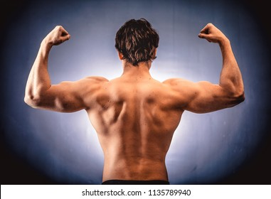 Back view of athletic shirtless man demonstrating beautiful muscles of back and shoulders.