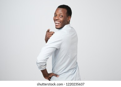 Back view of attractive african man looking with happy smile in camera turning back and pointing with finger at camera, isolated on white background. It was you, I saw it,
