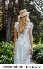 back view of attractive girl in white dress and wicker hat walking in forest