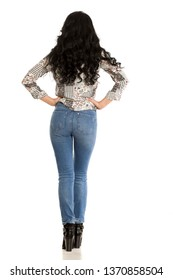 Back view of attractive woman in jeans posing on white background