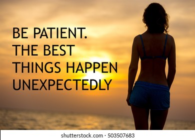 """Back view of attractive young woman standing at sea coast looking at picturesque colorful sunrise or sunset sky. Motivational text """"Be patient. The best things happen unexpectedly"""""""