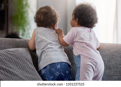 Back view of baby boy and girl standing together on back of couch, cute playing playdate interaction