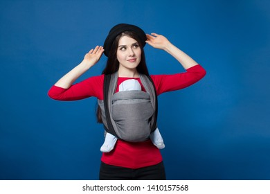 back view of babywearing attractive young mother with baby in woven wrap carrier fixing her hat. Free hands and active motherhood concept idea