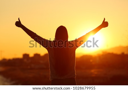 Back view backlight silhouette of a woman raising arms with thumbs up to the sun at sunset