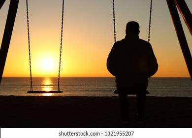 Back view backlighting silhouette of a man sitting on swing alone looking at sunset on the beach