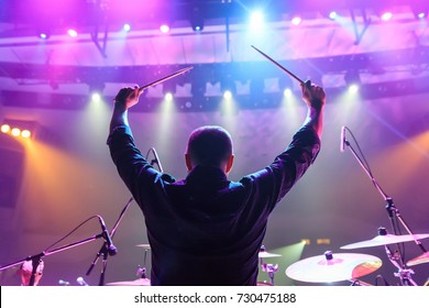 A back view of a band member playing drums  during a concert. Hands up with drum stiks.