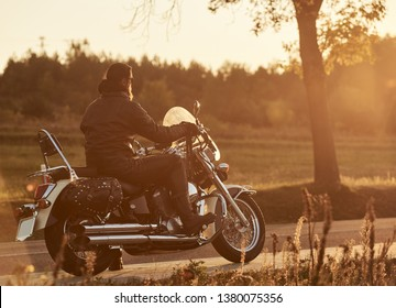 Back view of bearded biker riding cruiser motorcycle along empty narrow country road at sunset on beautifull golden autumn evening landscape background.