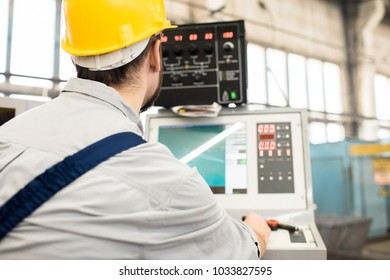 Back view of bearded operator wearing protective helmet focused on work while sitting in front of CNC machine, interior of production department on background