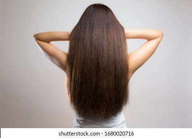 Back view of beautiful brown haired woman on gray background.