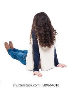 Back view beautiful curly woman sitting on floor and looks into distance. girl relaxes. Rear view people collection. backside view of person. Isolated over white background.