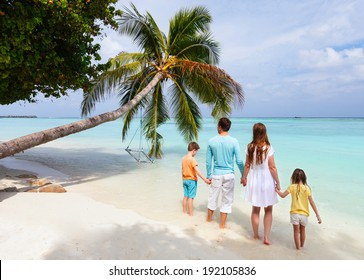 Back view of a beautiful family standing on a tropical beach with palm tree during summer vacation