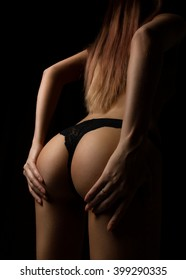 Back view of beautiful female bottom in lacy panties on a black background. girl holding herself  ass