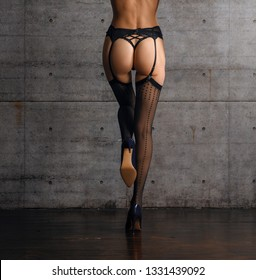 Back view of beautiful female legs in black stockings with belt and red high heel shoes. One leg up.