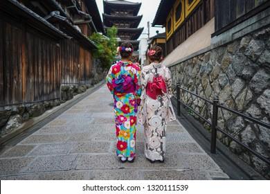 Back view of beautiful Japanese lady wearing Kimono with Yasaka Pagoda in background
