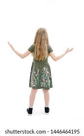 Back view of beautiful little girl in dress looking at wall and holds hand up. young blonde girl standing. Rear view people. Isolated on white background.