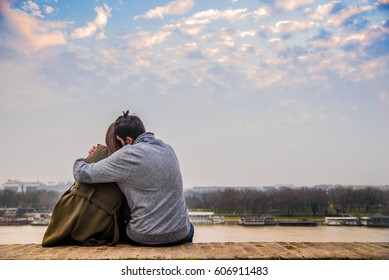 Back view of beautiful love couple sitting outdoors, looking the sky. Romantic teenage couple looking at blue sky. The lovely couple in love sitting under clouds. Carefree bright future concept.