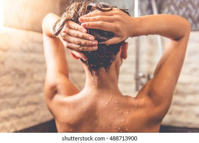 Back view of beautiful naked young woman taking shower in bathroom