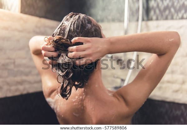 Back view of beautiful naked young woman washing her hair while taking shower in bathroom