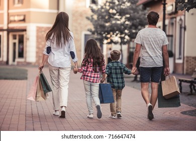Back view of beautiful parents and their cute little kids carrying shopping bags and holding hands while walking down the street