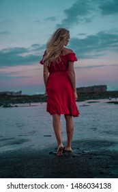 Back view of beautiful sensual woman in red dress posing on the black sand beach during sunset