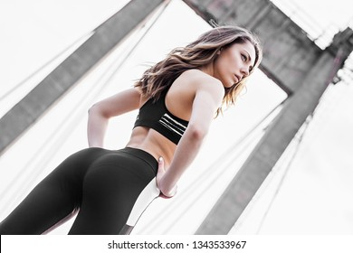 Back view of beautiful sexy sports woman in stylish sportswear standing on bridge. Attractive confident fitness girl with perfect butt and hips posing outdoors. Woman with sexy slim booty, ass