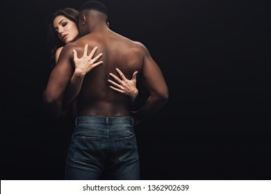 back view of beautiful sexy woman hugging shirtless african american man isolated on black