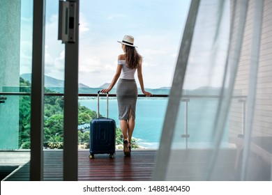 Back view: A beautiful tourist with a luxurious figure in a hat poses with her luggage on the balcony, which offers a beautiful view of the sea and mountains. Travel and vacation concept.