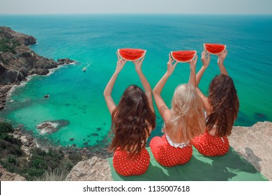 Back view of Beautiful traveller girl friends having fun with red watermelon on cliff mountains enjoying lagoon bay over Fiolent, Crimea. Three young women resting on a beach. Travel lifestyle.