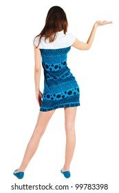 Back view of Beautiful woman in blue dress looking at wall and Holds a hand up. young brunette girl standing. Rear view people. Isolated over white background.