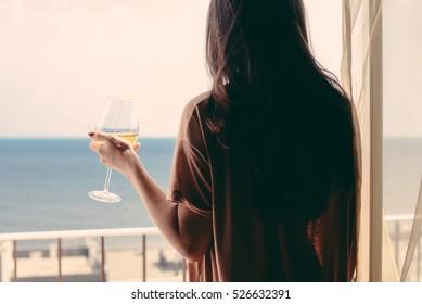 Zurück Blick auf die schöne Frau luxuriös entspannend genießen Glas Wein auf blauem Himmel Meer Außenhintergrund