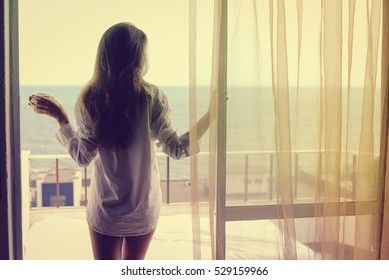 Back view of beautiful woman luxury relaxing enjoying cup of coffee tea on blue sky sea outdoors background