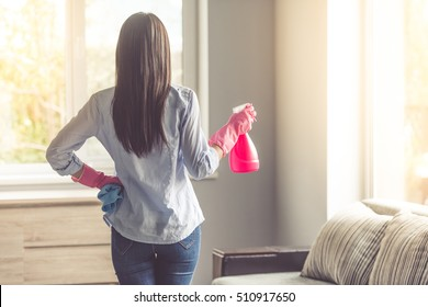Back view of beautiful woman in protective gloves holding a spray and a rag while cleaning her house