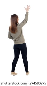 Back view of beautiful woman welcomes. Young teenager girl in dress hand waving from. Rear view  people collection. Isolated over white background. A girl in a gray jacket waving palm of right hand.
