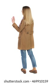 Back view of beautiful woman welcomes. Young teenager girl in jacket hand waving from. Rear view  people collection.  backside view of person.  Isolated over white background.  The blonde in a brown