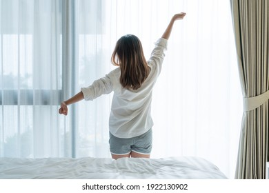 Back view of beautiful young Asian woman in white pajamas stretching after wake up in the morning in bedroom.