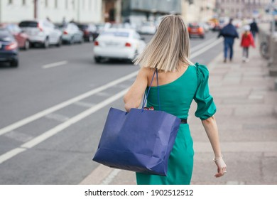 back view beautiful young blonde woman in a green dress with a large blue paper bag walks along the road along the sidewalk in the city