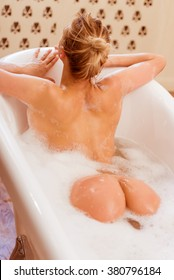 Back view of beautiful young blonde woman enjoying pleasant bath with foam, showing buttocks