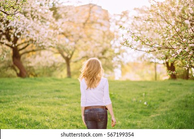 Back view of beautiful young blonde woman walking on a blossoming garden.